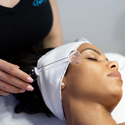 Female client getting high frequency facial in Los Angeles at Face of Jules